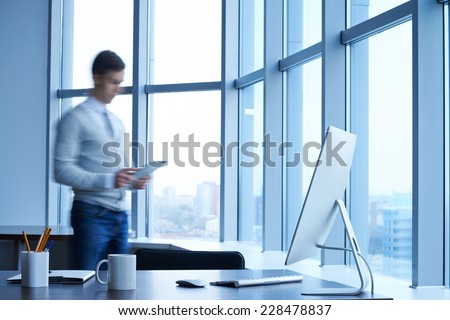 Workplace with computer with young businessman standing near by - stock photo