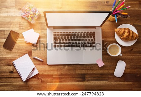 Workplace with notebook, office supplies and wooden desk. - stock photo