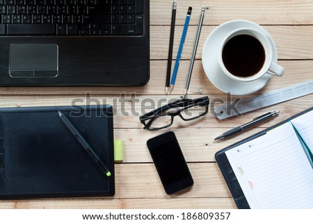 Workplace with notebook, Pen Graphics Tablet, keyboard, mouse pad, and cup of coffee on work table. Above view shot. - stock photo
