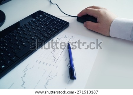 workplace with sheet of paper with statistics, tablet with ballpoint pen and a section of a keyboard - blue - stock photo