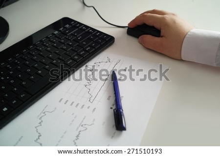 workplace with sheet of paper with statistics, tablet with ballpoint pen and a section of a keyboard - stock photo