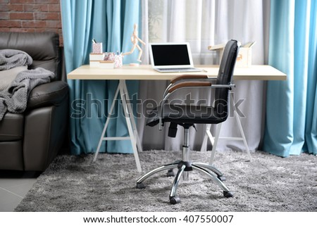 Workplace with table, laptop and office chair in living room - stock photo