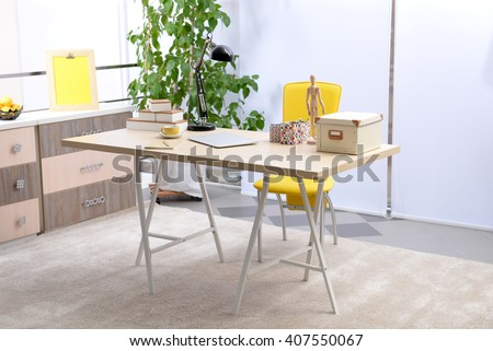 Workplace with table, yellow chair and laptop in living room - stock photo