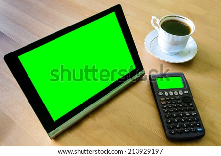 workplace with tablet pc - green box, calculator and cup of coffee - stock photo - stock photo