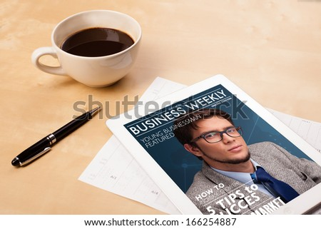 Workplace with tablet pc showing magazine cover and a cup of coffee on a wooden work table close-up - stock photo