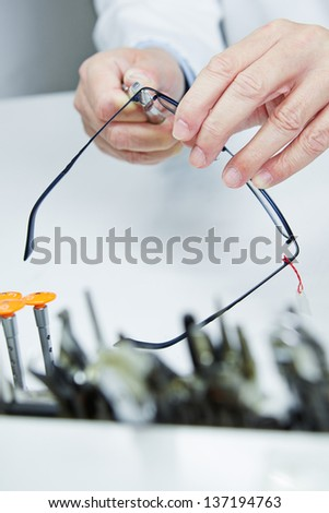 Workshop repair of glasses through hands of an optician - stock photo
