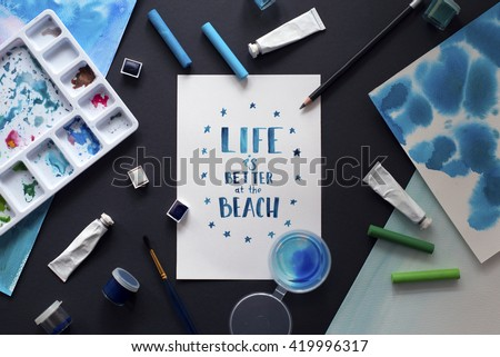 workspace artist on black background. paint, palette, watercolor, brushes, paper. Top view lettering. hand drawn calligraphy. Life is better at the beach. creative graphic poster for your design.  - stock photo