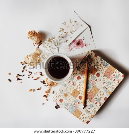 Workspace. Cup of black coffee, sketchbook, pencil, two watercolor cards and beige dried roses isolated on white background. Overhead view. Flat lay, top view - stock photo