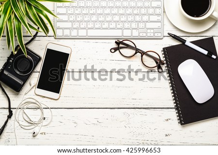 Workspace desk with keyboard, smart phone, camera, earphone, eyeglasses, notebook, pen, mouse, cup of coffee and tree, Office desk with essentials working stuff - stock photo