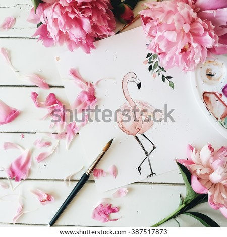 Workspace. Pink flamingo painted with watercolor, paintbrush and pink peonies isolated on white background. Overhead view. Flat lay, top view - stock photo