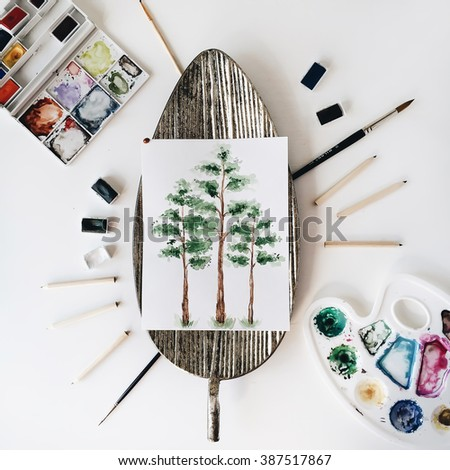 Workspace. Three trees painted with watercolor on golden tray, paintbrush and pencil isolated on white background. Overhead view. Flat lay, top view - stock photo