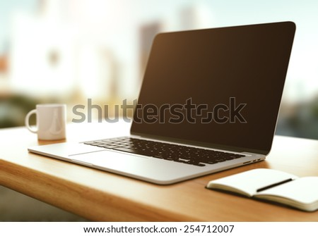 workspace with modern laptop at sunrise - stock photo
