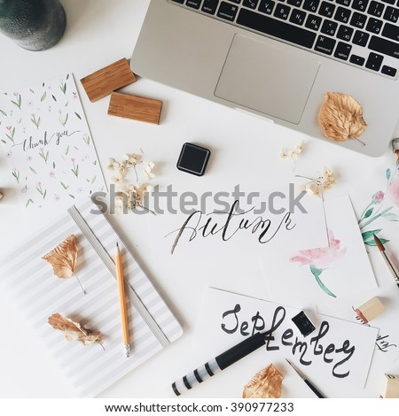 "Workspace. Words ""Autumn"" and ""September"" written in calligraphy style, sketchbook, laptop, pencil, postcard and beige dried leaves isolated on white background. Overhead view. Flat lay, top view - stock photo"
