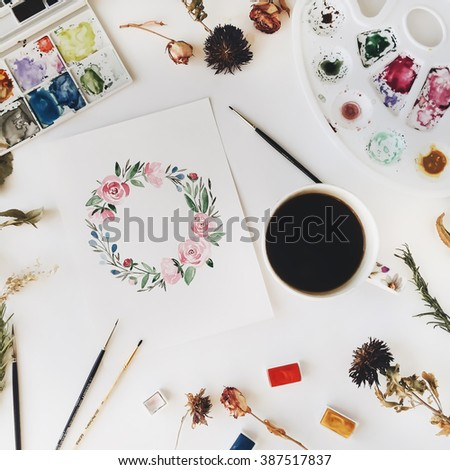 Workspace. Wreath with flowers and leaves painted with watercolor, paintbrush and cup of black coffee isolated on white background. Overhead view. Flat lay, top view - stock photo