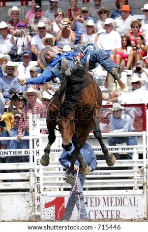 World Champion Bareback rider, Kelly Timberman, makes a successful ride at the 2005 Cheyenne Frontier Days rodeo. - stock photo