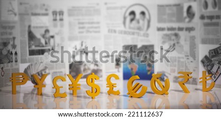 World currency units front of newspaper's economy pages - stock photo