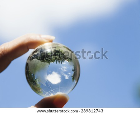 World environmental concept. Crystal globe in human hand on a blue sky background. Visible are the continents the Americas. Selective focus on the reflection. - stock photo