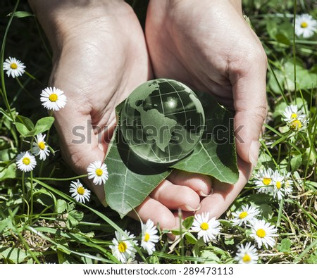 World environmental concept. Crystal globe in human hands. Visible are the continents the Americas - stock photo