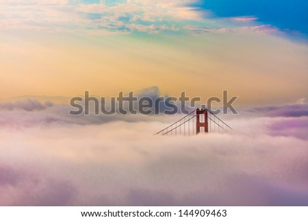 World Famous Golden Gate Bridge Surrounded by Fog after Sunrise in San Francisco,California - stock photo