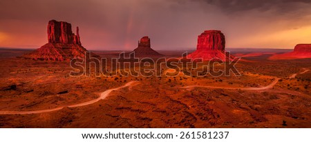 World famous Monument Valley mesas with a colorful sunset before the storm - stock photo