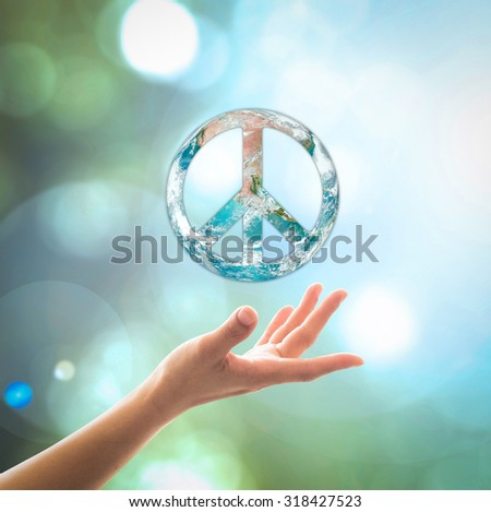 World globe with peace sign shape over female human hands with blurred abstract background of natural greenery bokeh: International day of peace concept: Elements of this image furnished by NASA - stock photo
