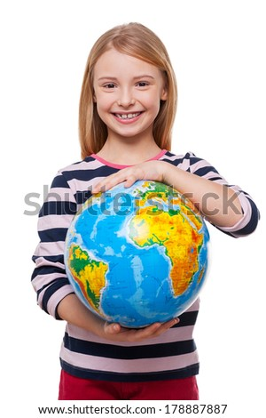 World in my hands! Cheerful little girl holding a globe and smiling while standing isolated on white - stock photo