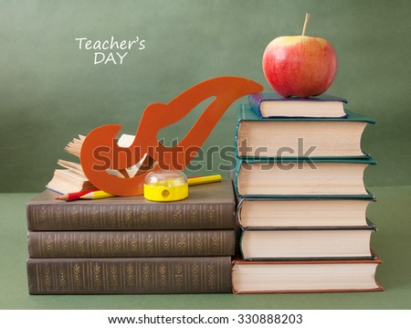 World Teacher's Day (still life with book pile, apple, globe and desk on artistic background) - stock photo