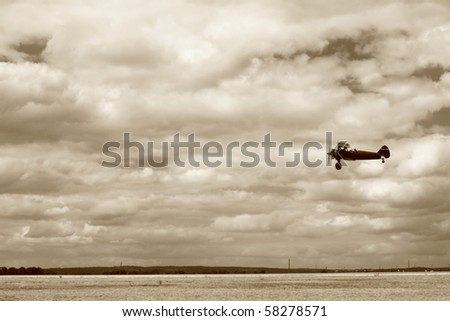 World War II fighter flying at low altitude, performing a fly-by. The ground is not totally crisp because of a slight panning. No sharpening was applied. - stock photo