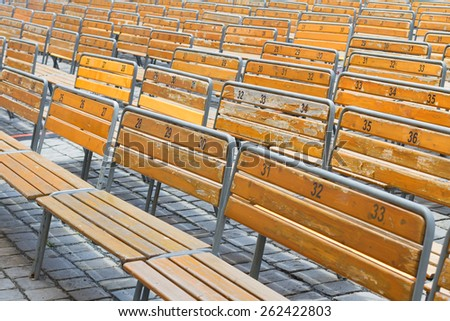Worn out benches at open air auditorium in rows - stock photo