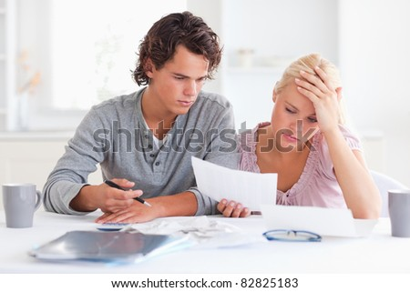 Worn out couple listing expenses in the living room - stock photo