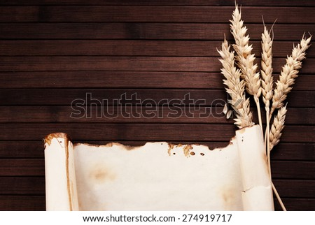 Worn out paper scroll and few ears of wheat on wooden background. - stock photo