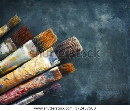 Worn painting brushes on dark green zinc background. Vintage effect.  - stock photo