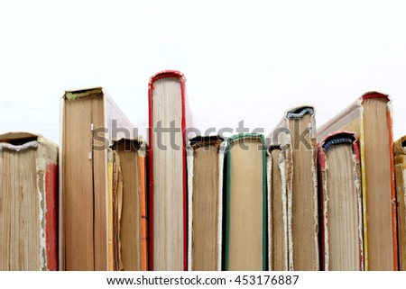 Worn various books stand on shelf of the library light, top view / literature that is in demand - stock photo
