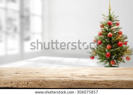 worn wooden desk space and xmas tree of red balls  - stock photo