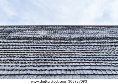 Worn wooden roof shingle of old house against sky - stock photo