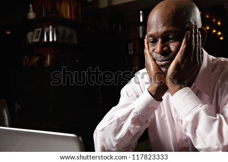 Worried african guy in pink shirt sitting at laptop - stock photo