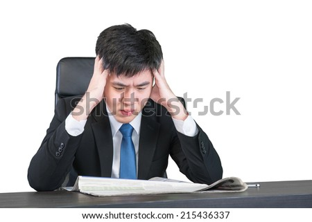 Worried Asian young businessman sitting with head in hands at office desk with clipping path - stock photo
