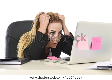 worried attractive businesswoman in stress working with laptop computer at office desk overwhelmed and overworked suffering collapse in frustrated face expression pulling her blond hair - stock photo