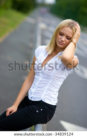 worried blonde woman on the street - stock photo