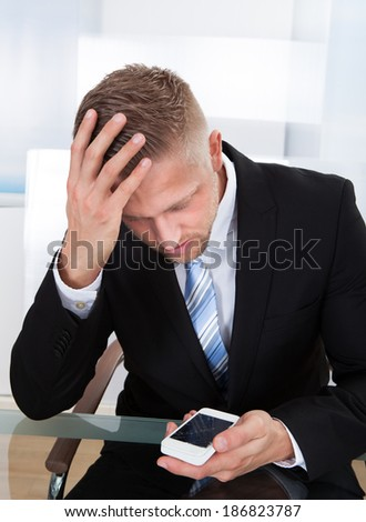Worried businessman checking a mobile message sitting with his head in his hand as he reads the text - stock photo