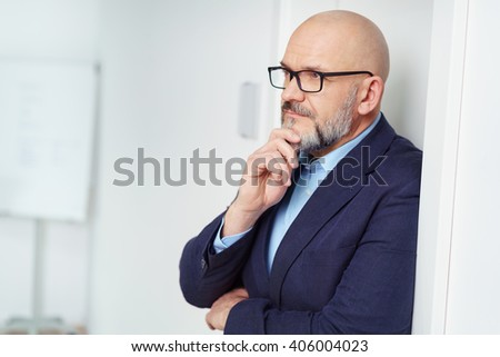 Worried businessman leaning against the wall in the office with his hand to his chin staring into the distance - stock photo