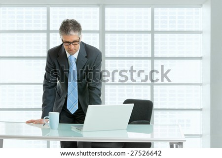 Worried businessman leaning on office desk with laptop computer on it,  looking down. - stock photo