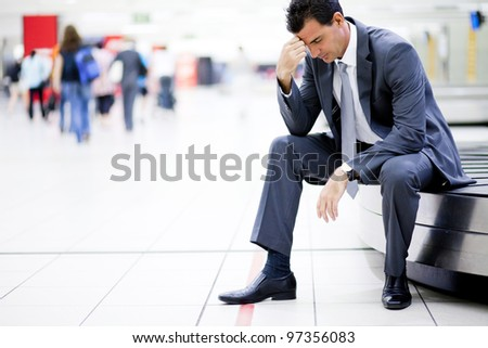 worried businessman lost his luggage at airport - stock photo