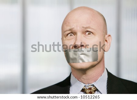Worried businessman silenced with duct tape over his mouth - stock photo