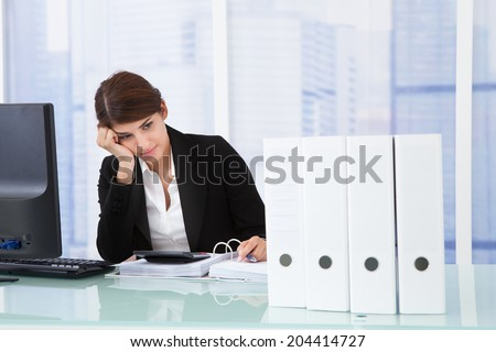 Worried businesswoman looking at binders on office desk - stock photo