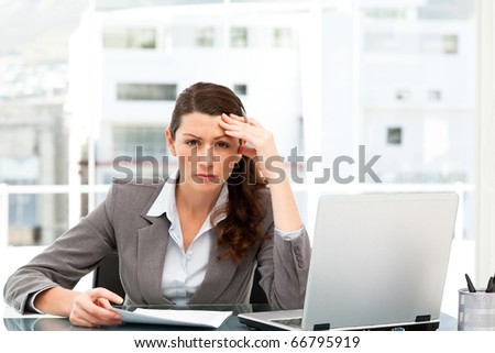 Worried businesswoman working at her desk with laptop and folder - stock photo