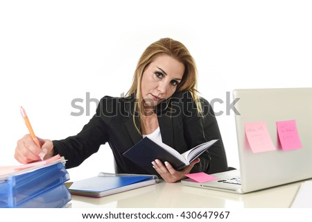worried busy attractive businesswoman in stress working with laptop computer talking on mobile phone multitasking at office desk overwhelmed and overworked  - stock photo
