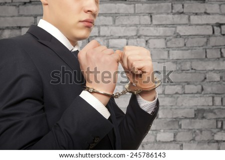 Worried caucasian middle aged businessman in handcuffs - stock photo