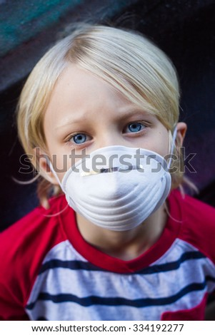 Worried child wearing protective face mask to stop infection  - stock photo