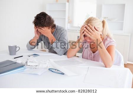 Worried couple doing accountsin their living room - stock photo